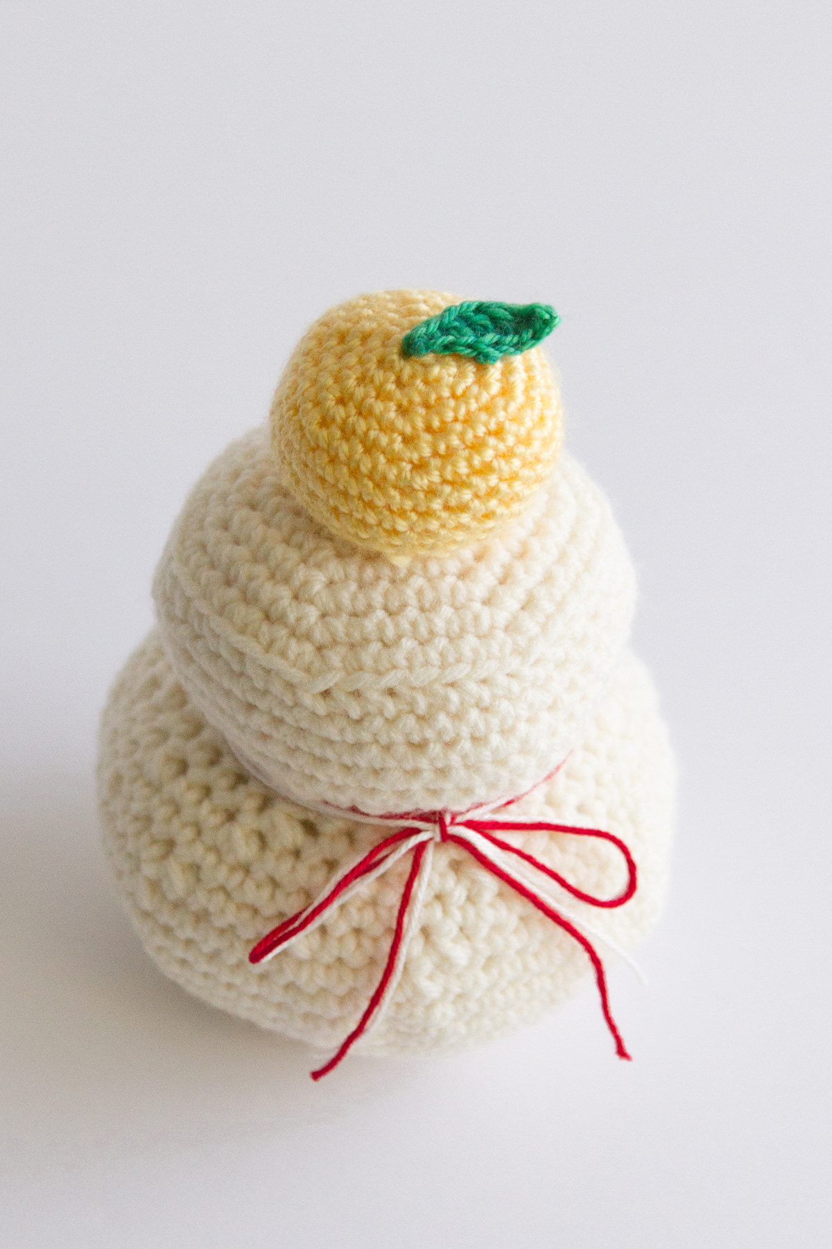 Crocheted Kagami-mochi. Mochi (sticky rice cakes) with a tiny Japanese orange (similar to Mandarin oranges) on top.
