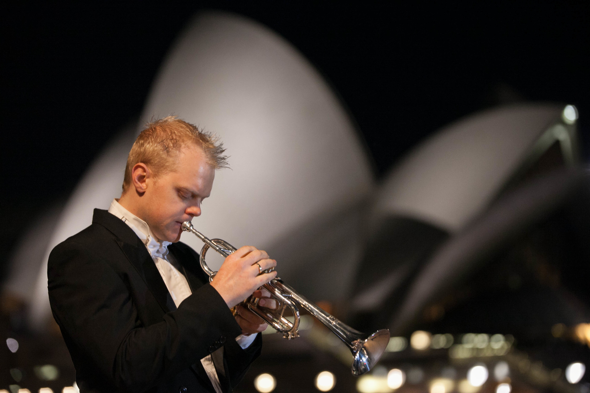 Trumpeter Phill O'Neill standing in front of the Sydney Opera House