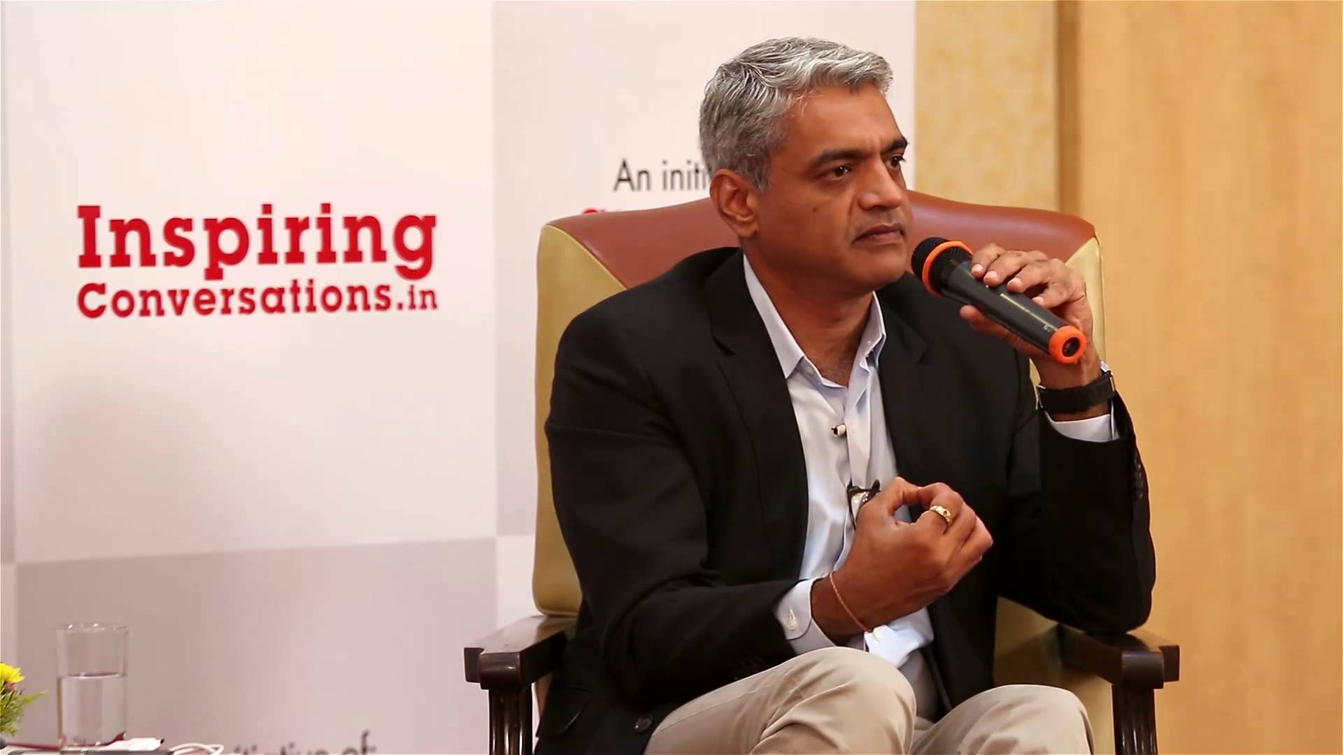 Pictured above is Captain Raghu Raman - a former CEO of the Indian National Intelligence Grid and military officer, sitting in a chair while holding a microphone and acting as a guest speaker at an event. In the wall behind him there is a caption saying 'inspiring conversations.in'.