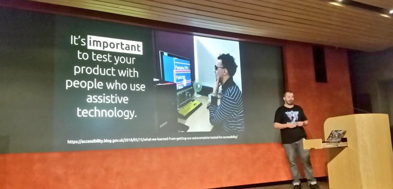 """Craig Abott pictured giving his 'Empathy in Accessibility' talk. The slide behind him says: """"it's important to test your product with people who use assistive technology' and contains a picture of a colleague doing just that at a computer desktop."""