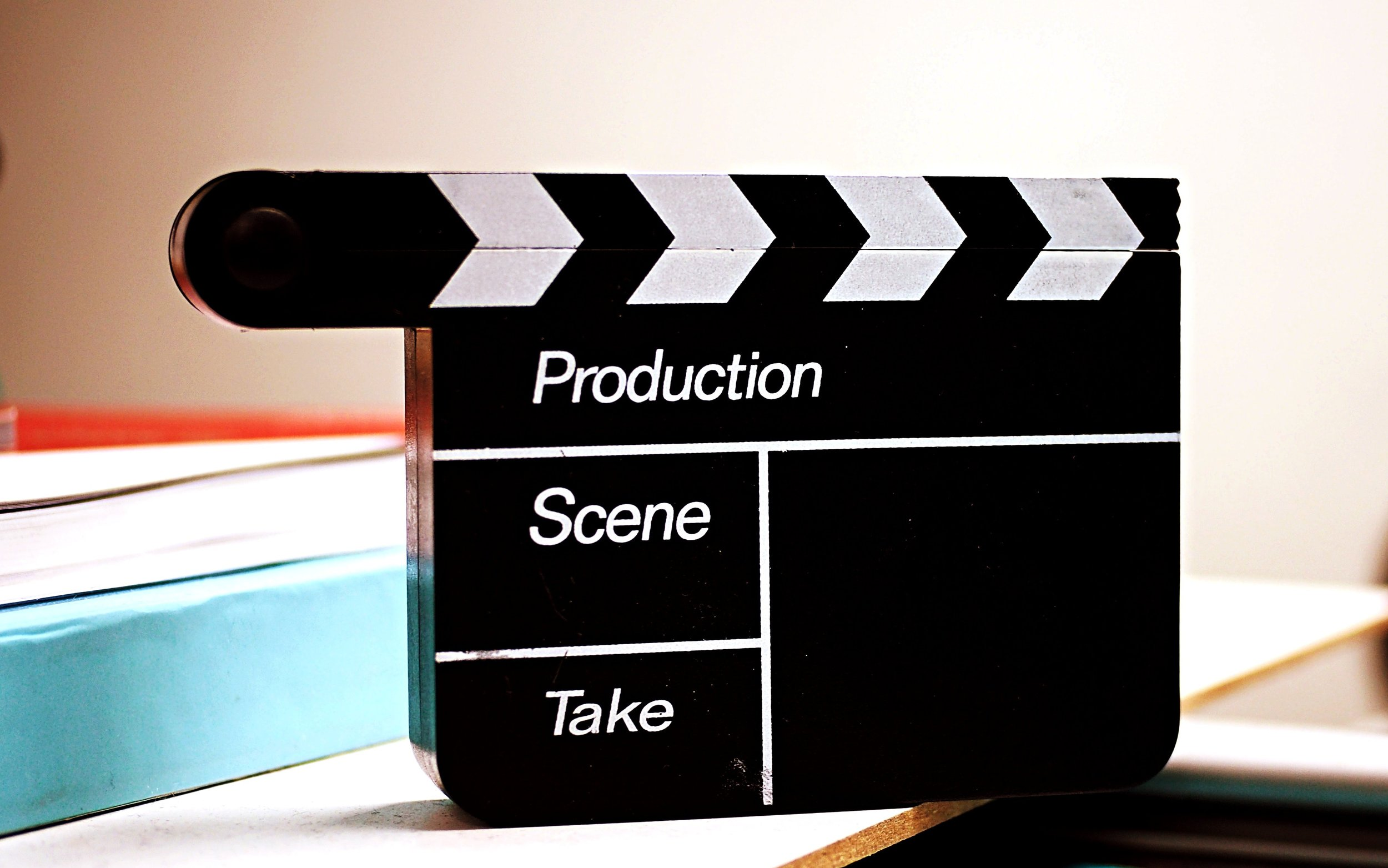 Clapperboard sitting on a desk with 2 books behind it