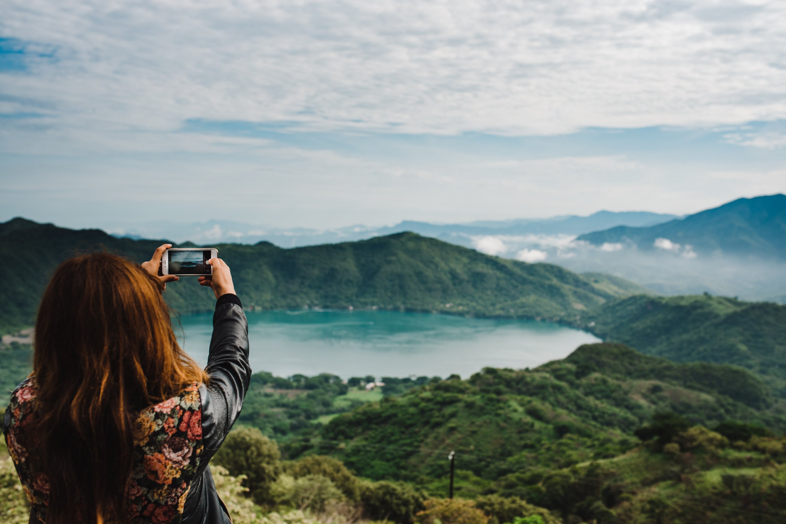 Photographer taking a picture of a mountain and the lake below it during the day time