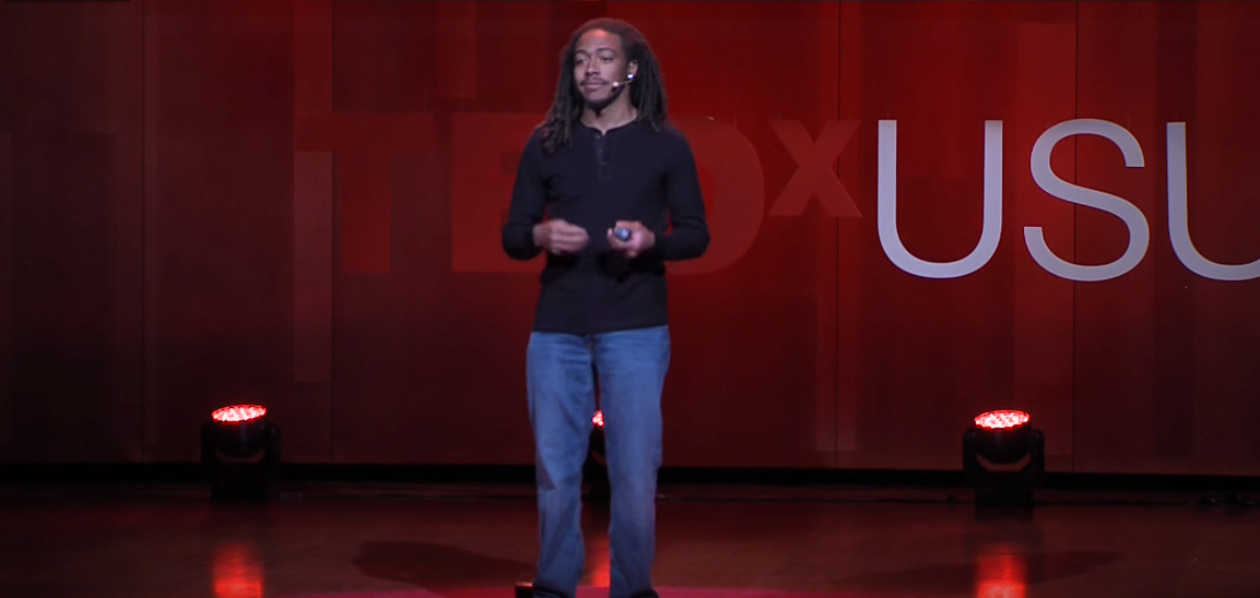 Salif Mahamane is standing on a red coloured stage giving a Ted Talk about dyslexia and how an environment can effect its symptoms.