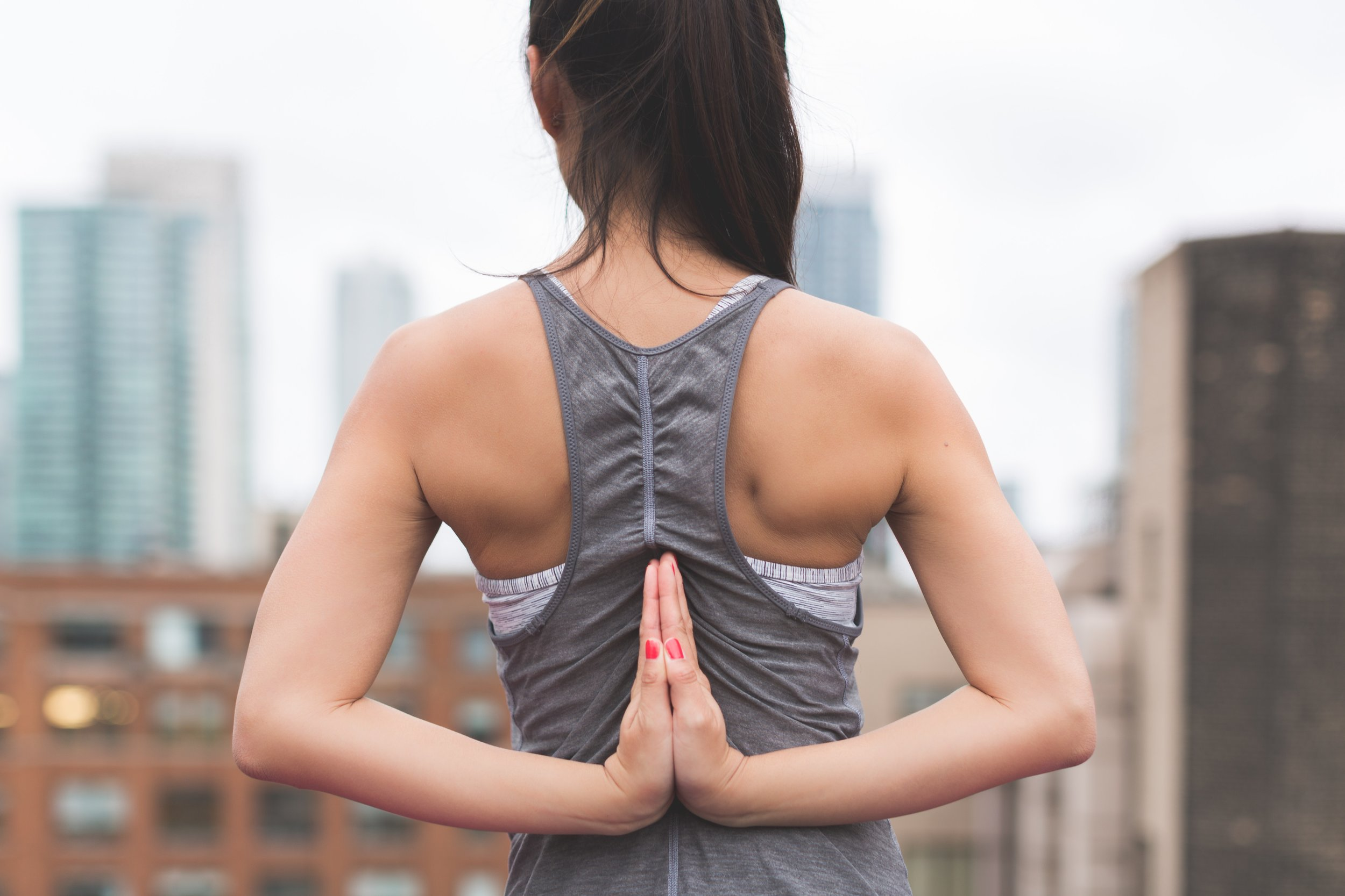 An adult standing on the roof of their office building facing skyscrapers and folding their hands behind their back to do yoga exercises. This helps them concentrate on their work when they return from lunch.