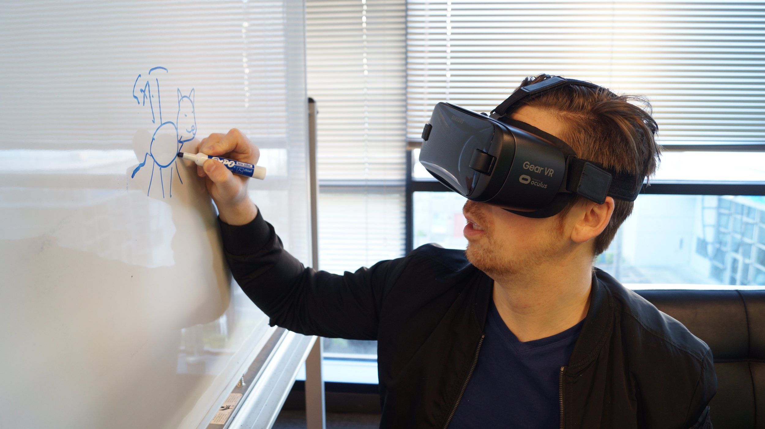 A facilitator using a VR headset while writing on a whiteboard
