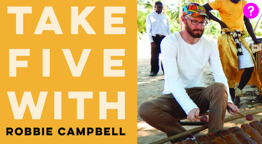 Take Five With Robbie Campbell - pictured is Robbie playing a type of xylophone music from Mozambique called timbila, with two people standing behind him