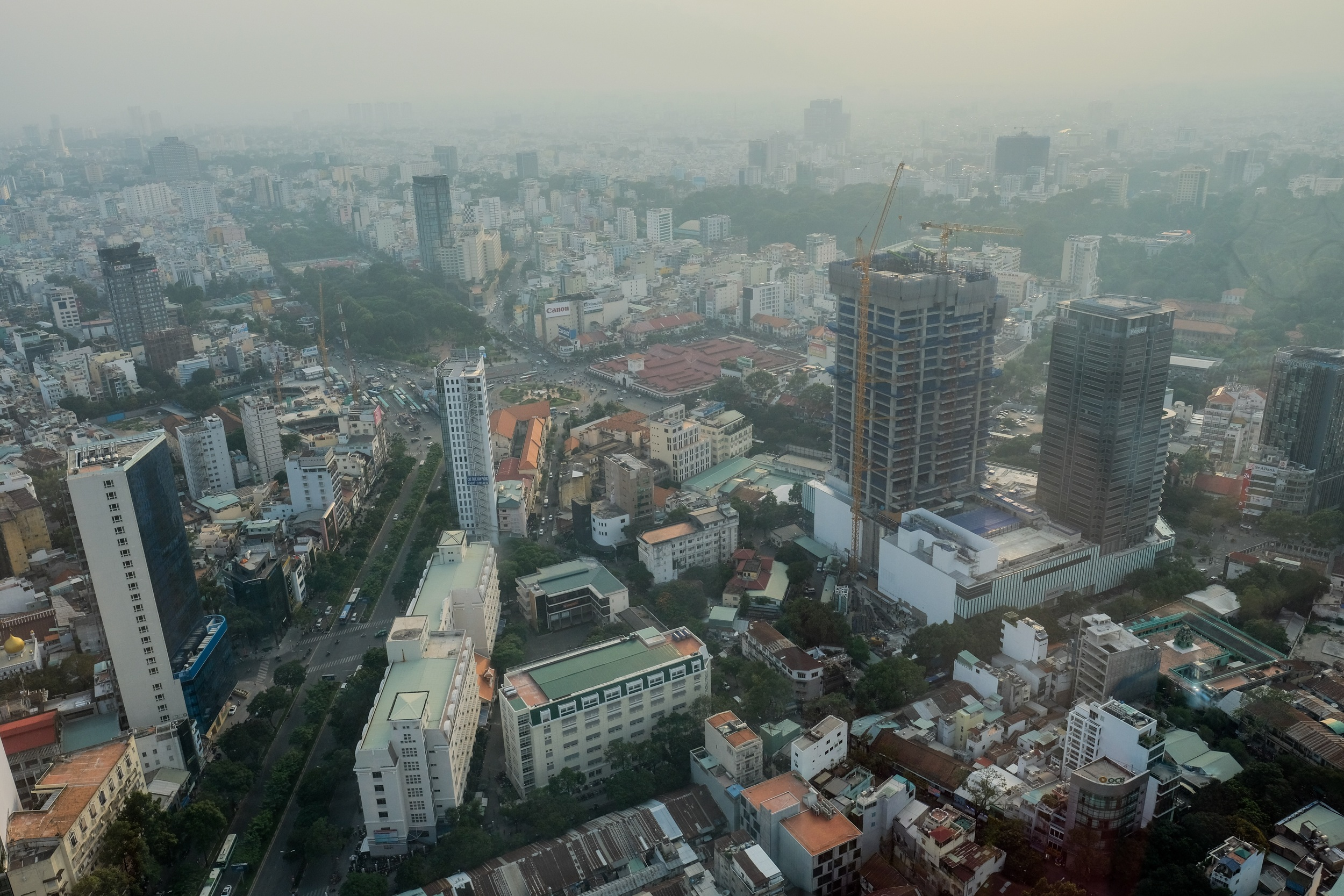 The western side of District 1, with Ben Thanh Market to the left of the building under construction and the backpacker area on Pham Ngu Lao and Bui Vien Street along the left side of the park .