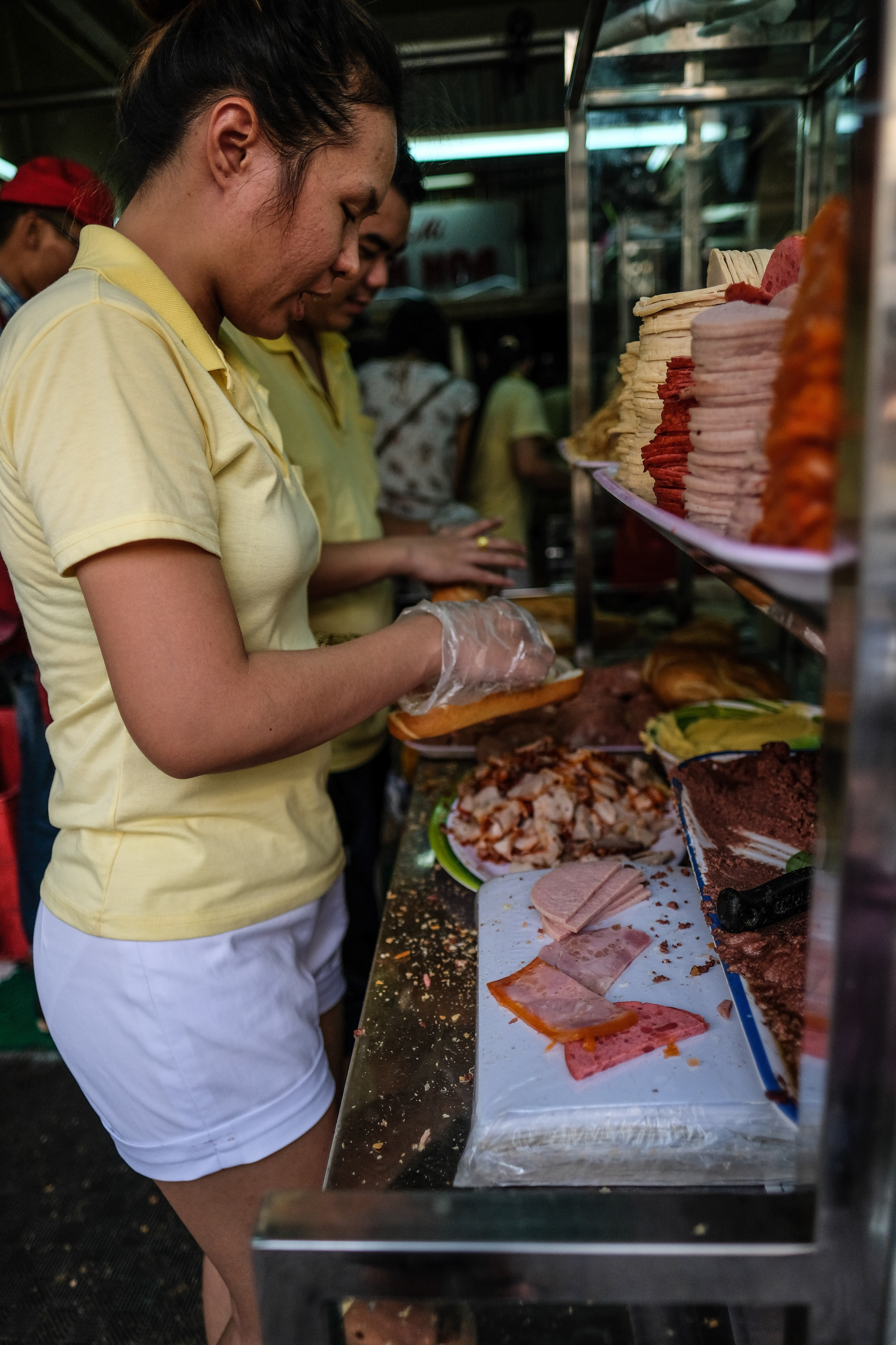 Preparing Banh Mi at the tiny but famous Banh Mi Huynh Hoa on Le Thi Rieng. It is a term for all sorts of bread, but is also used for the typical Vietnamese baguette with a variety of meats, a spread of pate, herbs and chillies.
