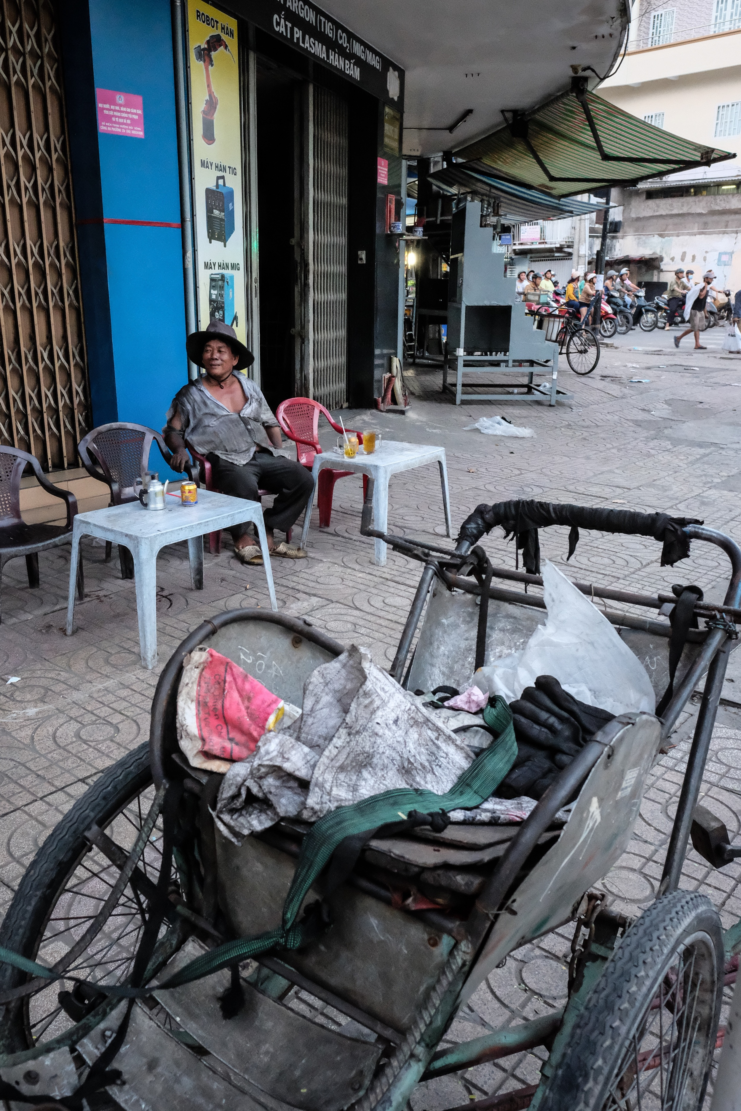 A cyclo driver enjoying a break and a cold beer.