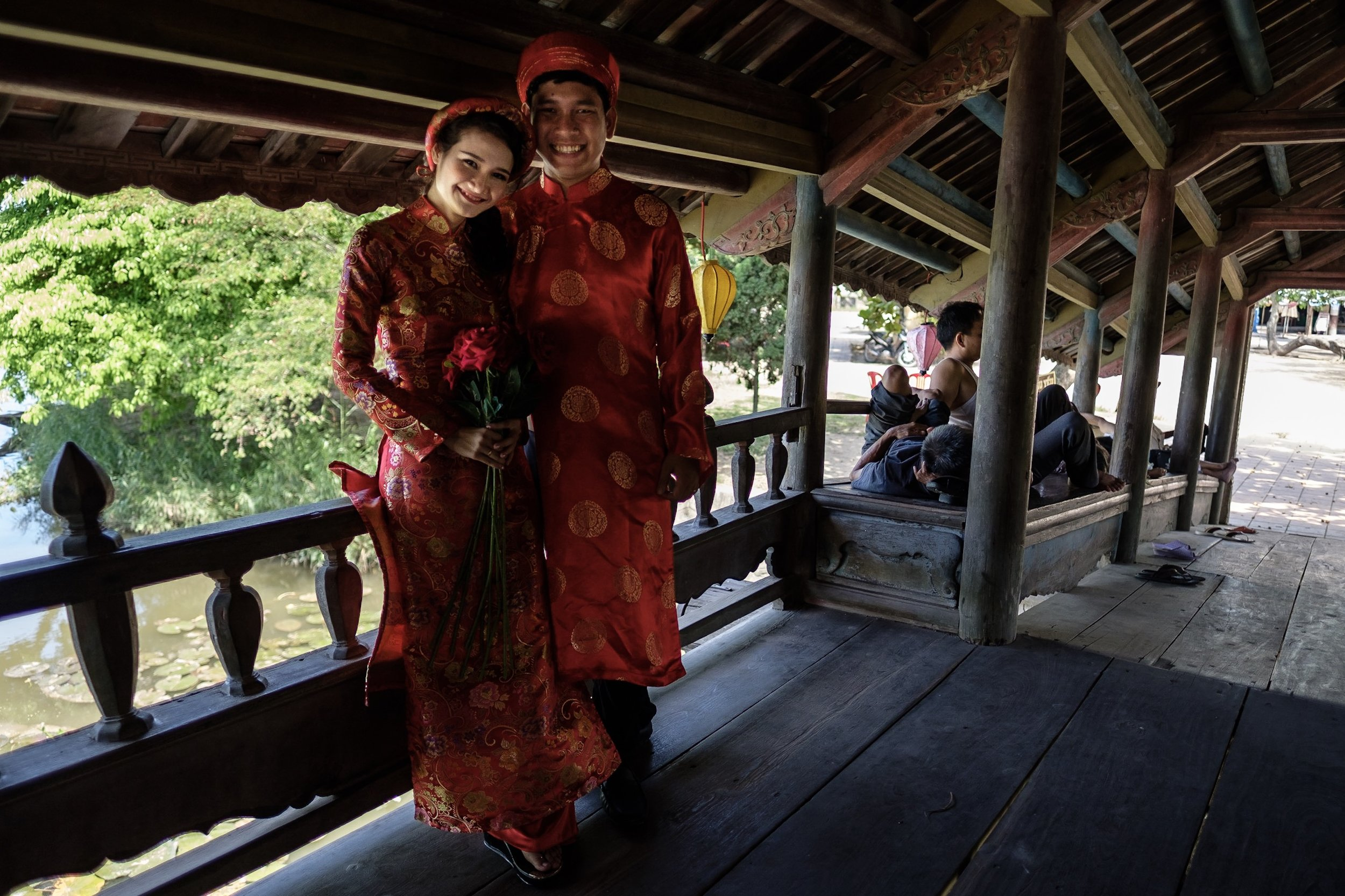 Newlyweds taking shelter from the sun on a bridge in a small village outside of Hue.