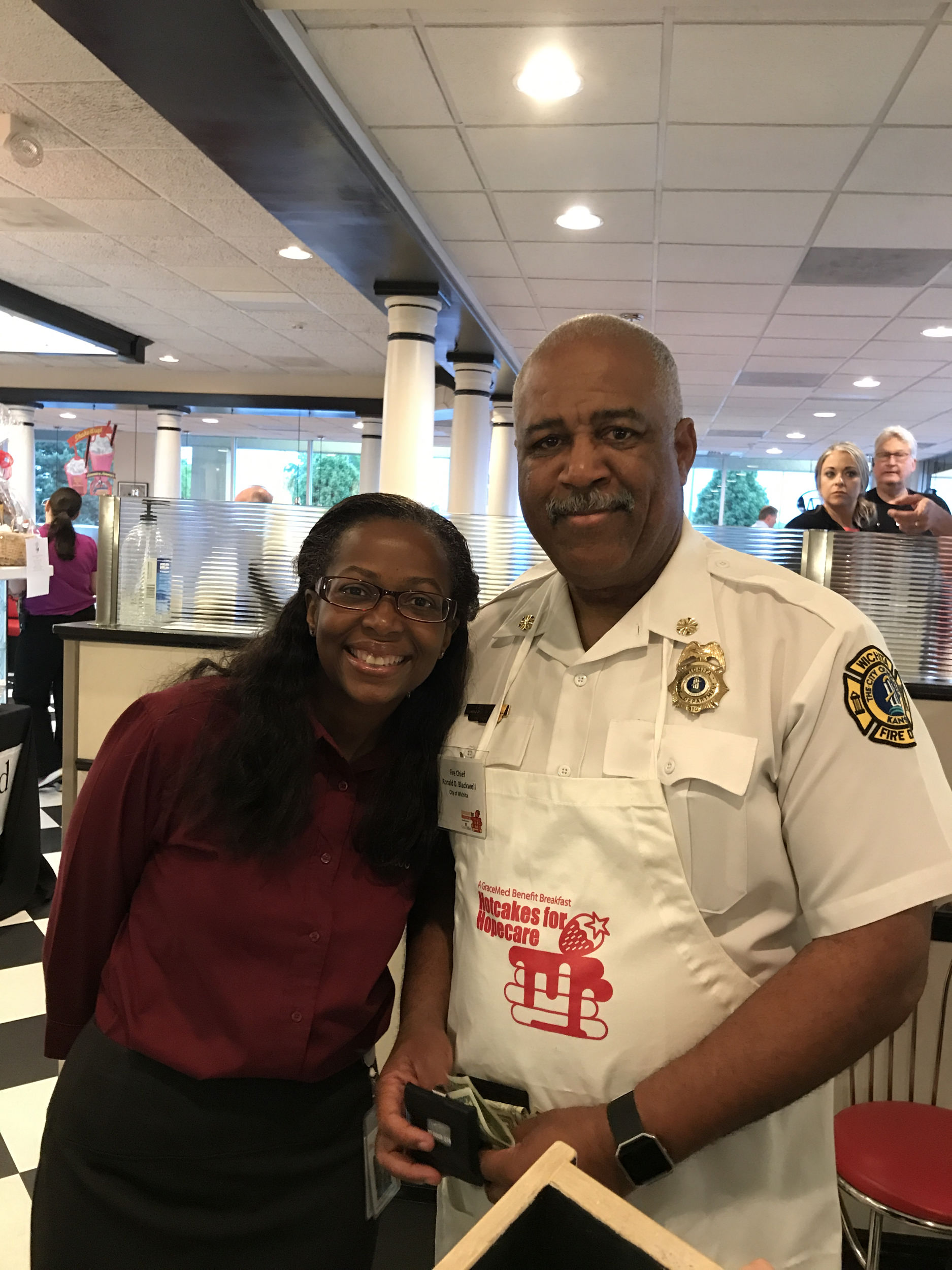 GraceMed Associate Executive Officer Venus Lee with Wichita Fire Chief Ron Blackwell