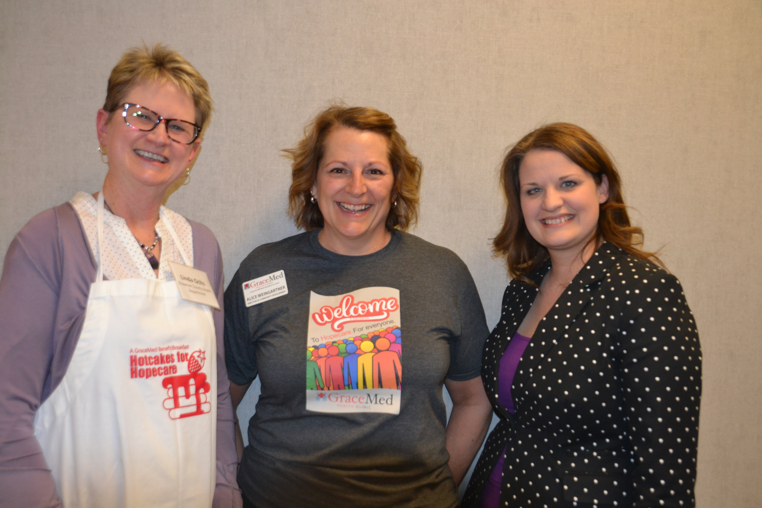 Linda Ochs from the Shawnee County Health Department, GraceMed's Alice Weingartner and Misty Kruger from Topeka Public Schools take a break from their food serving duties.