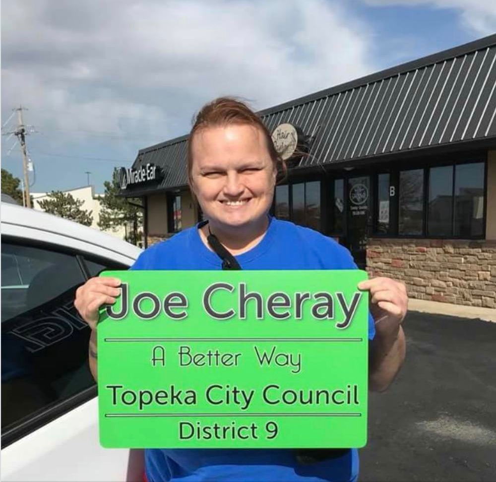 Joe holds a sign for her campaign for Topeka City Council. -