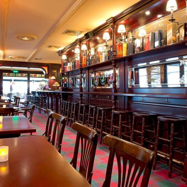 Koyu ahşap ve sergilenen viski ve bira şişeleri ile %100 pub dekoru