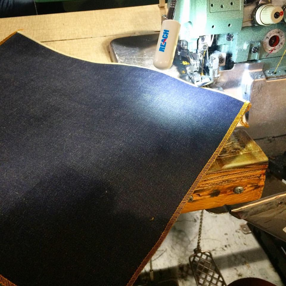George hand surging the hand cut denim back patches at the Raleigh Denim Workshop!