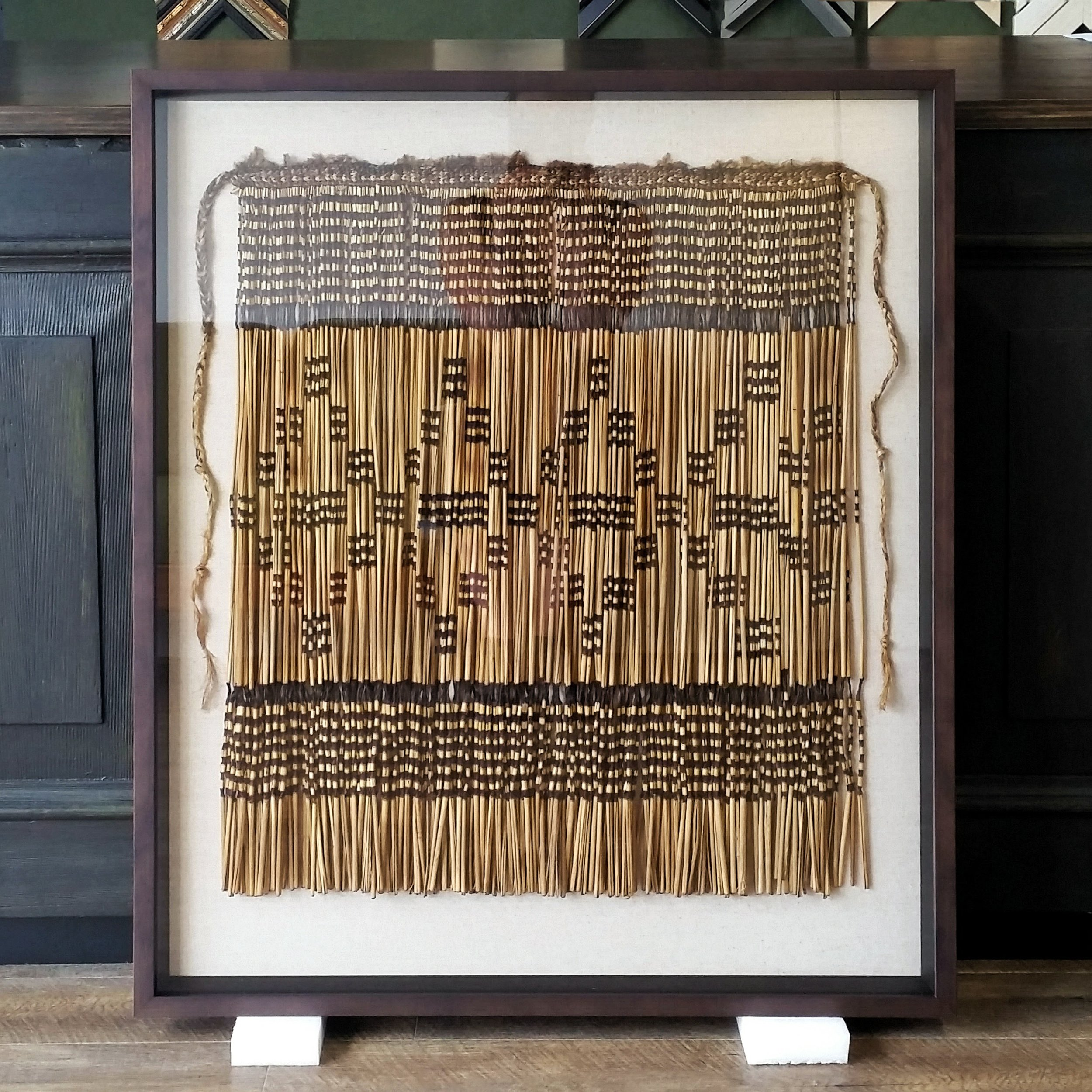 Nearly-100-year-old piupiu hand-stitched onto linen-covered backing, and box framed