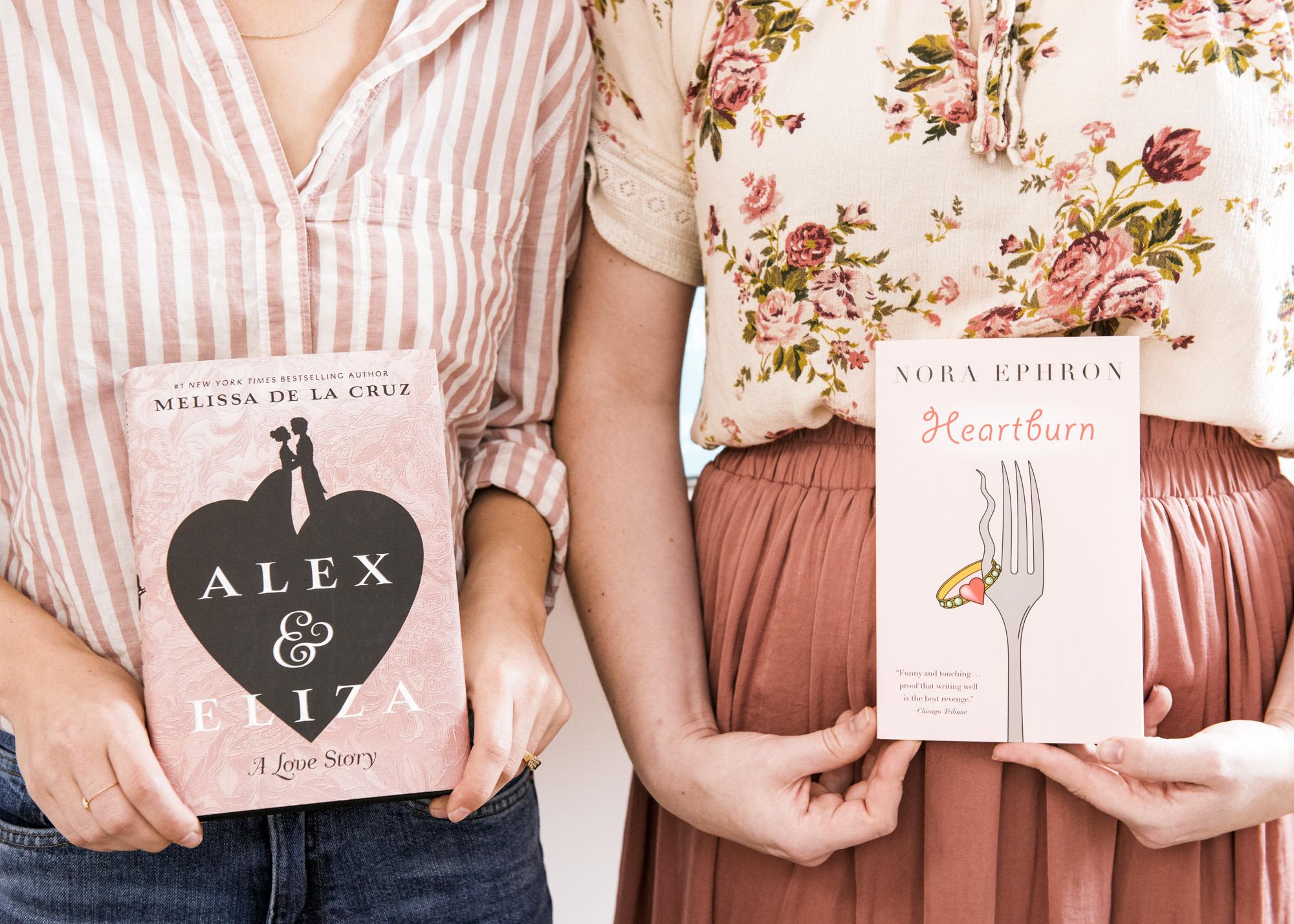 Bea (left) holding a copy of  Alex & Eliza , & Leah holding a copy of Nora Ephon's  Heartburn