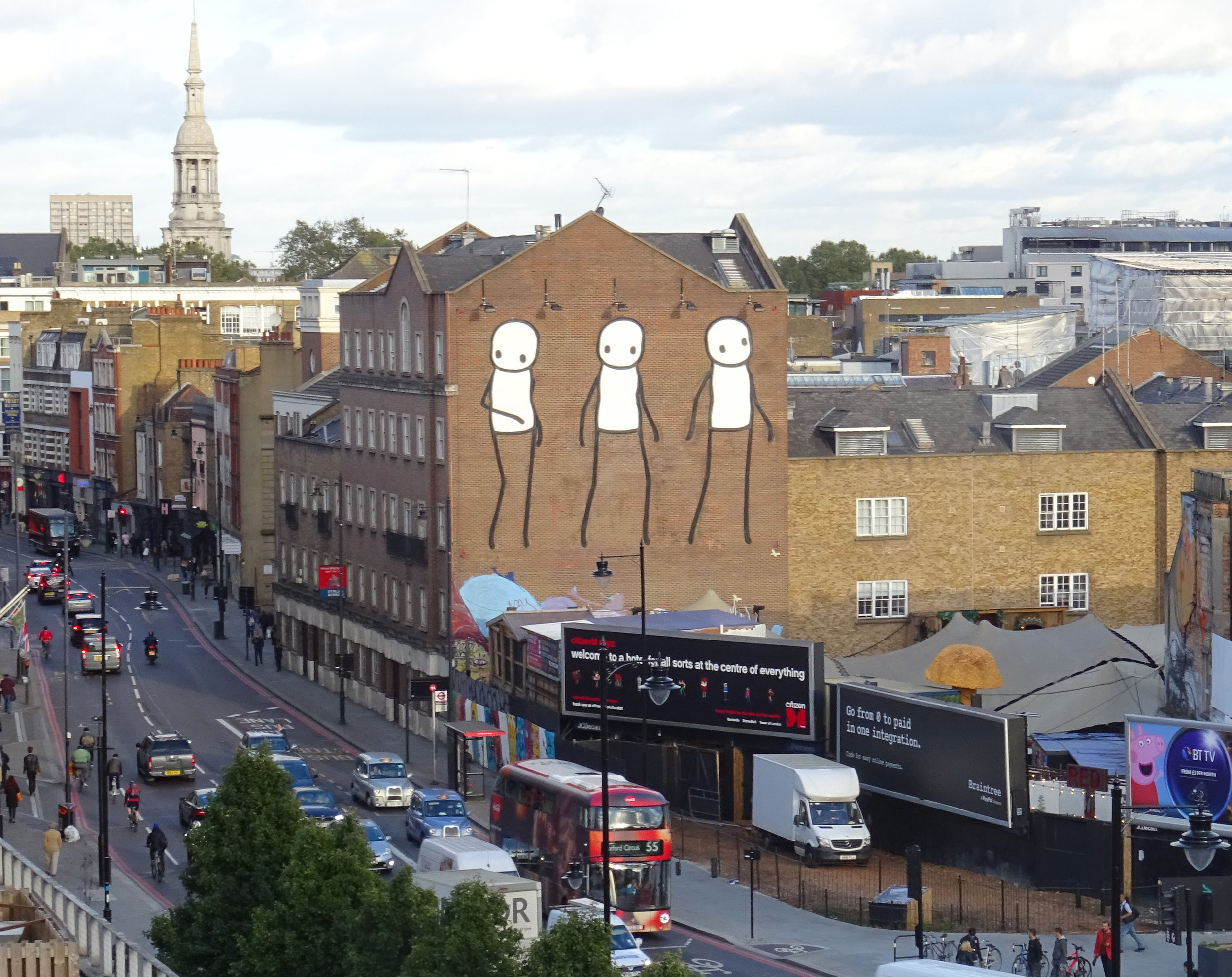 Past, Present and Future  Three figures representing the past, present and future of Shoreditch rise high over the former artists' district, home now to only a handful of artists. The first figure looks longingly back on Old Street where artists once thrived, the second peers out at the encroaching billboards, uncertain of how long the few remaining artists can afford to stay, the third teeters precariously, to succeed or move on is yet to be seen. This mural is intermittently obscured by an advertising hoarding and is visible only on certain weeks of the year.