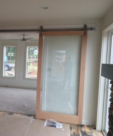 Floor to ceiling sliding glass barn door.