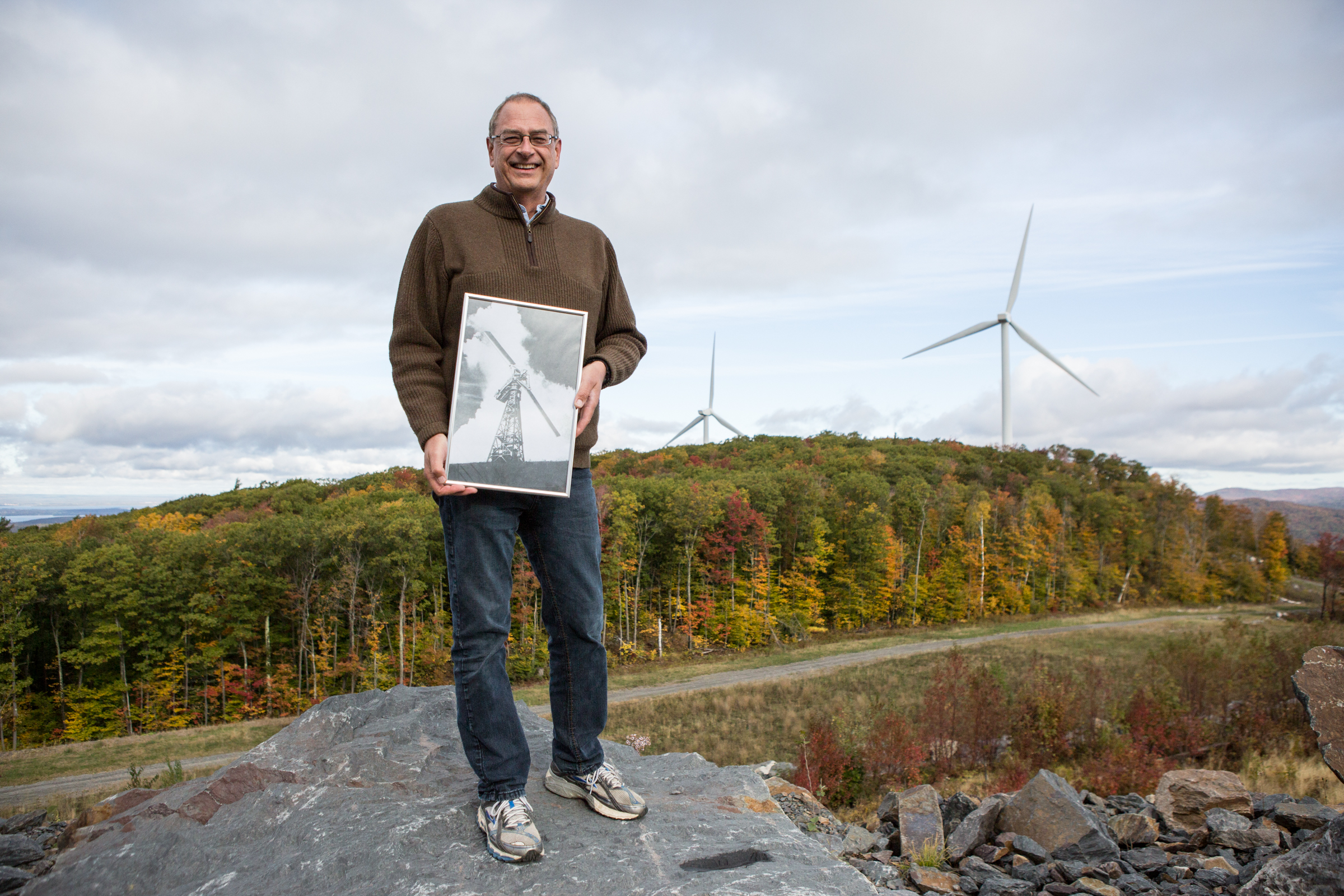 David Blittersdorf at the 10-megawatt Georgia Mountain Community Wind farm constructed in 2012 on the Milton-Georgia town border, holding an archival photo of the Smith- Putnam wind turbine–the world's first utility-connected wind turbine, which was built in 1941 atop Grandpa's Knob in Castleton, VT. Photo by Ned Castle.