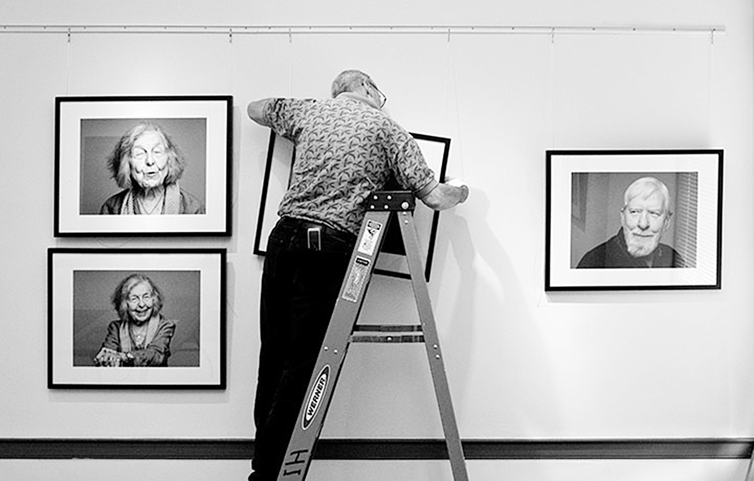 Bob Hooker, our Vision & Voice exhibit installer, hangs portraits in the main gallery.