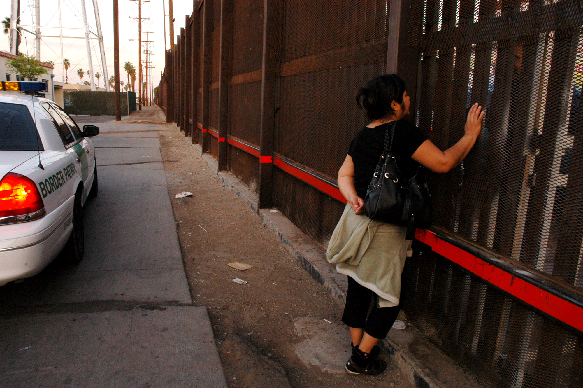 A woman (on the California side of the fence) meets her husband (on the Mexico side of the fence) to talk. She works in California, and does so legally, but while her permit and documents are being renewed she stays in the U.S. rather than return to Mexico every evening and risk not being able to be allowed back in the country to go to work the next day.