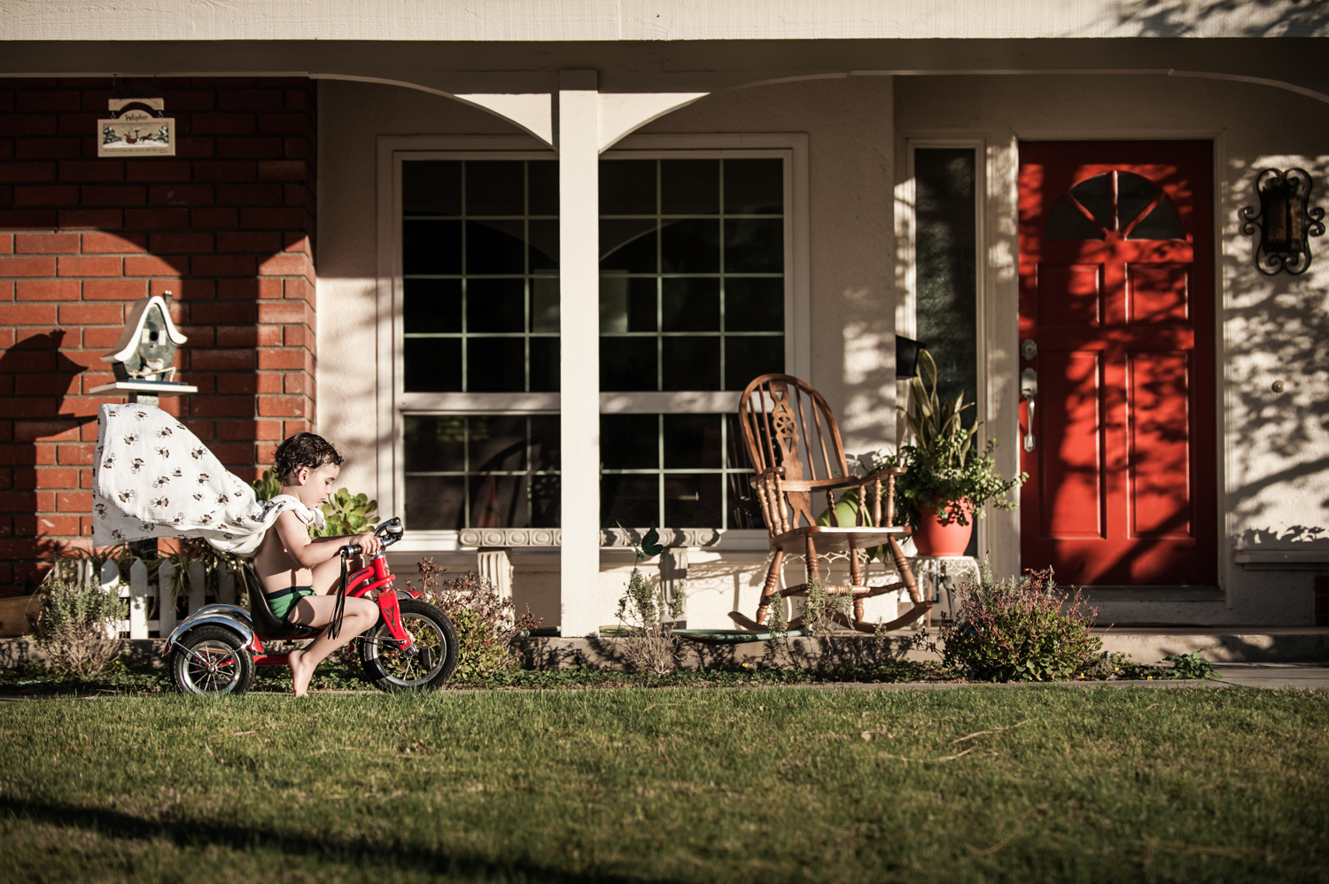 family home photo session tricycle red door cape superhero childhood