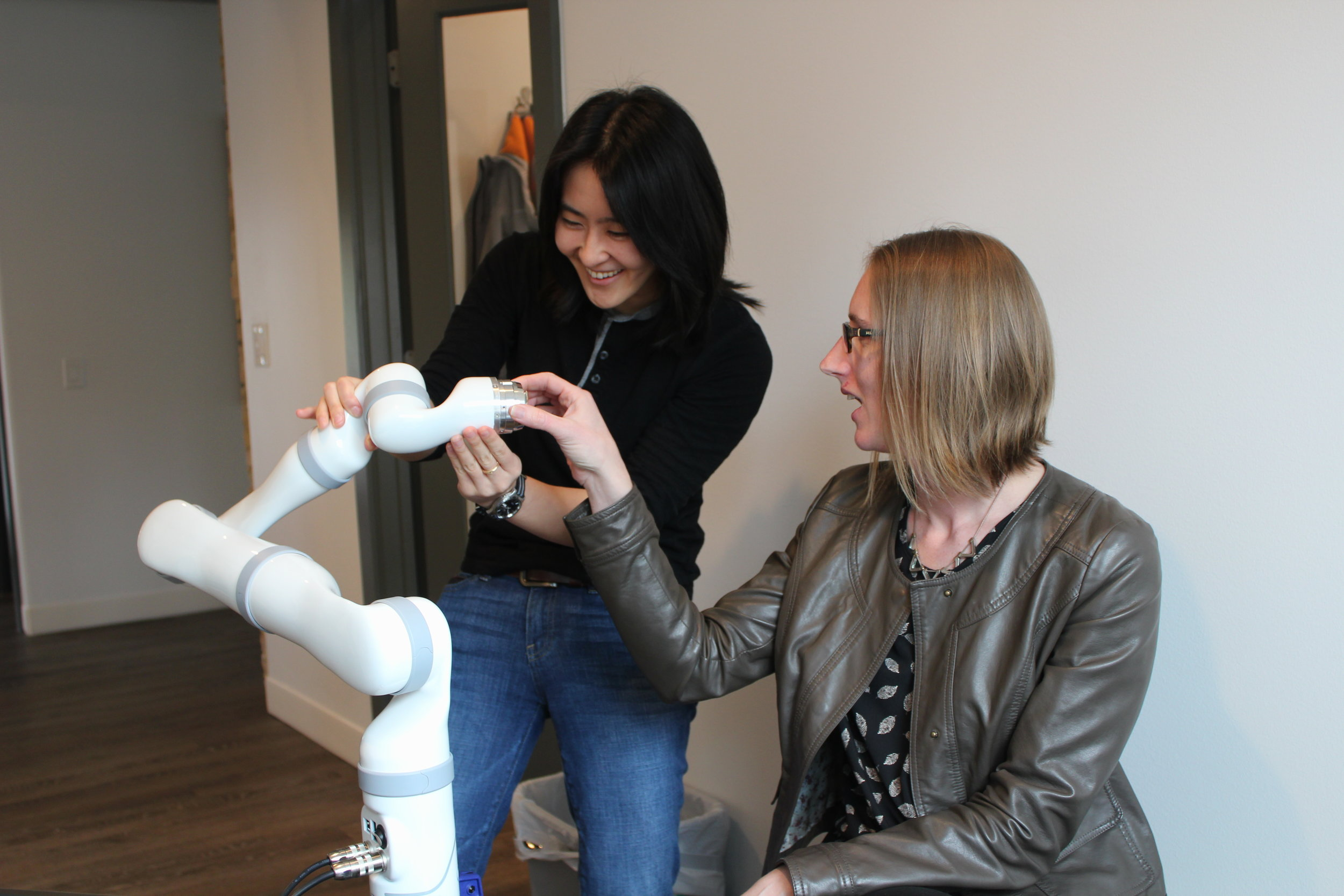 Diligent Robotics Co-Founders Vivian Chu (left) and Andrea Thomaz (right) with their original arm prototype for Moxi in NCV's offices.