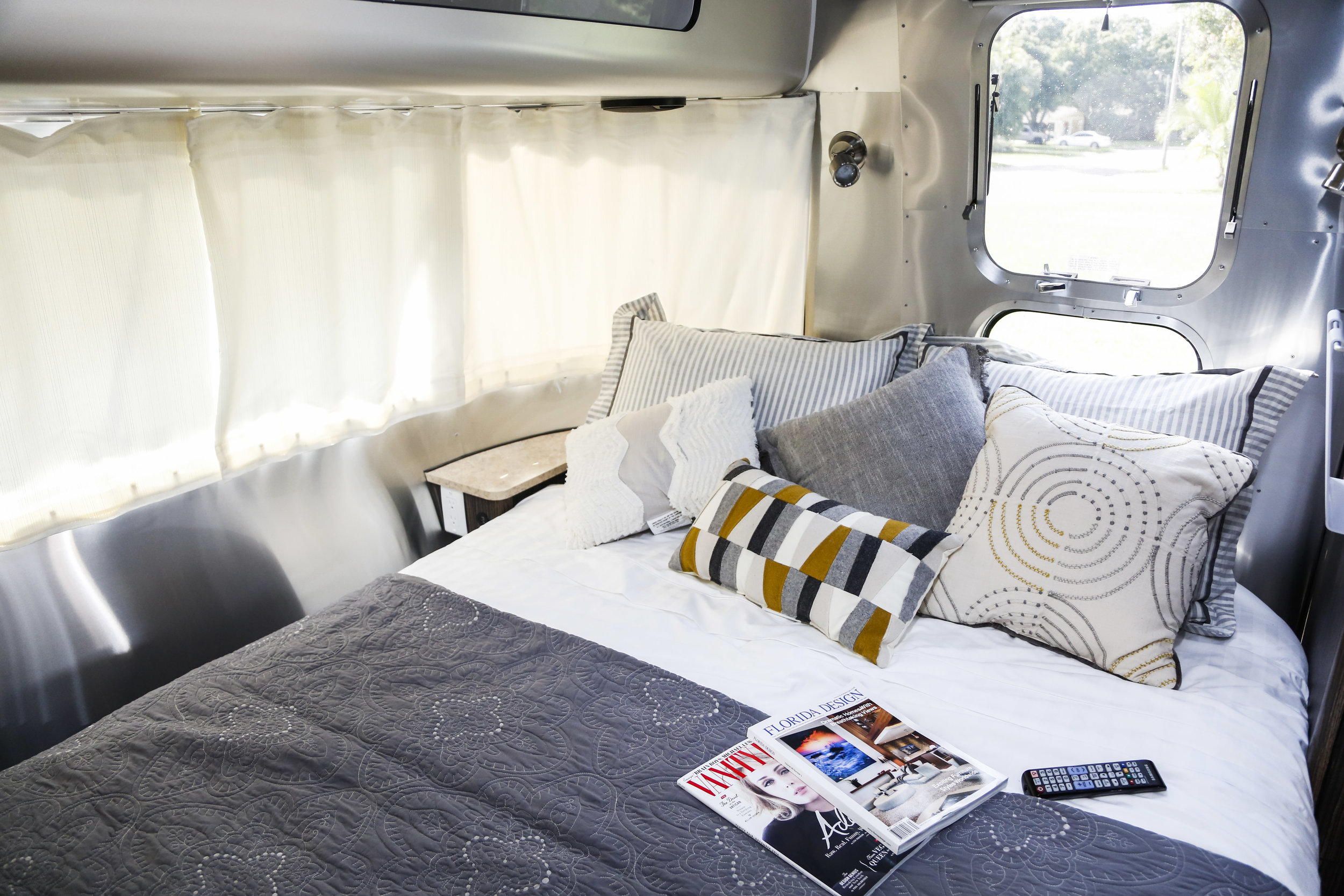 The bedroom features a premium queen bed and lots of natural light, but privacy curtains when you need them.