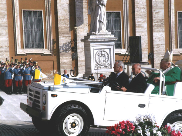 """Pope John Paul II enters the altar area in the """"Pope Mobile."""""""