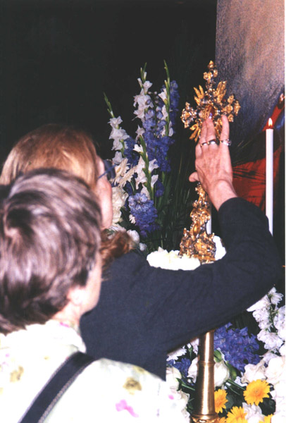 A pilgrim places a kiss from her fingers on the relic of Blessed Emperor Karl.