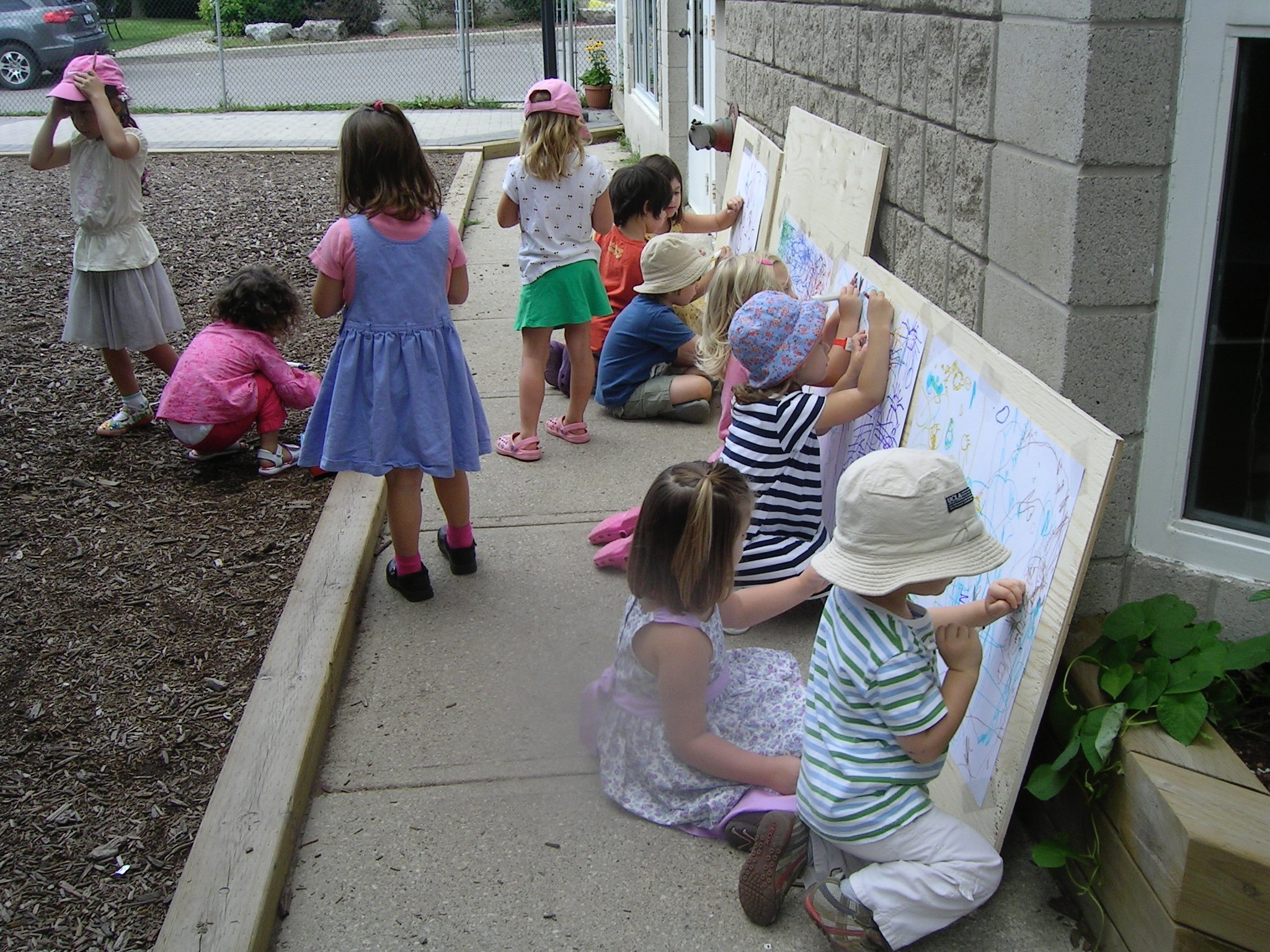 Children doing outdoor projects with markers and boards at Kaban Montessori in Mississauga.