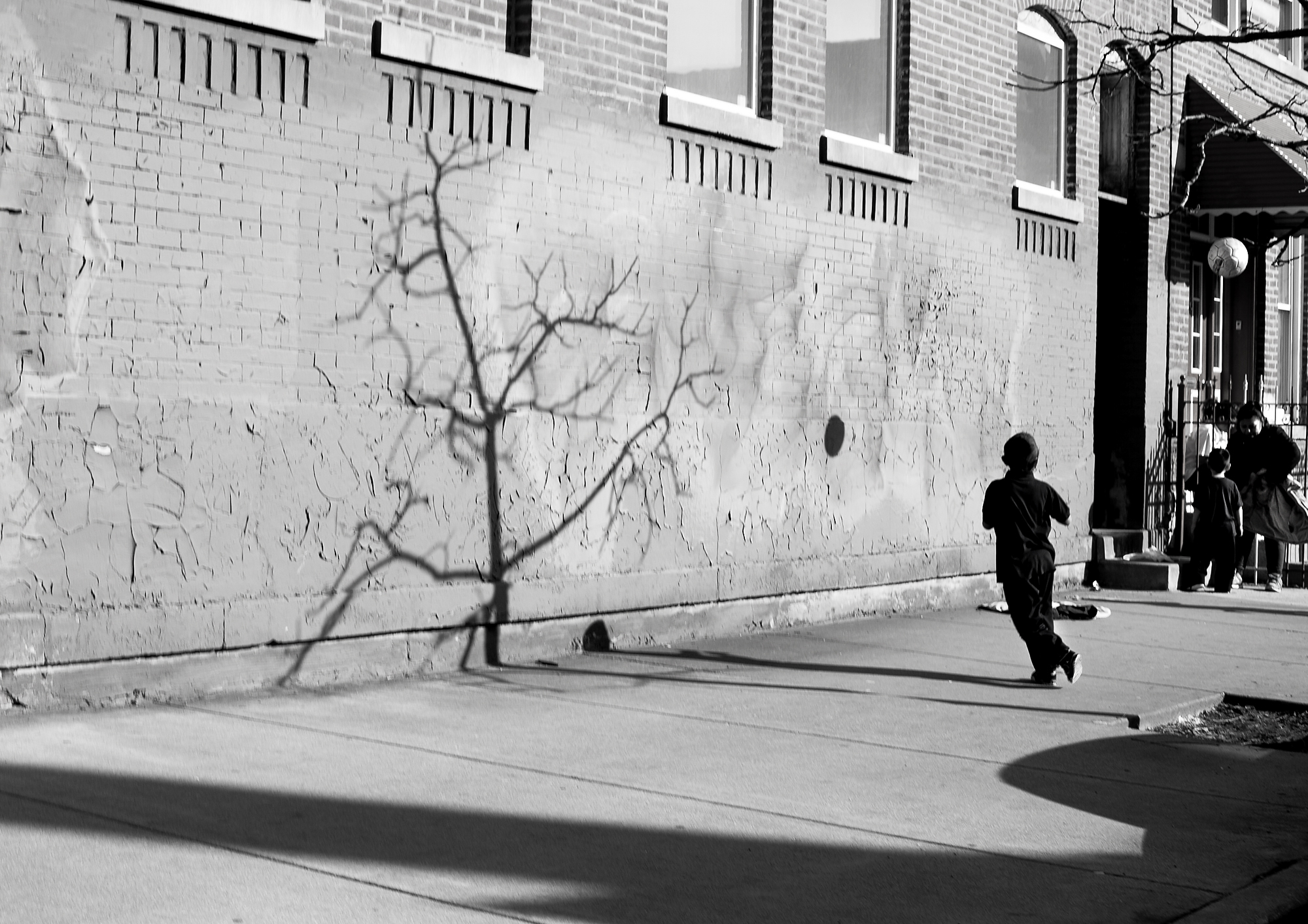 Kids in Pilsen playing soccer on the sidewalk after school during an unusually warm day in March. Photography by Eddie Quinones.