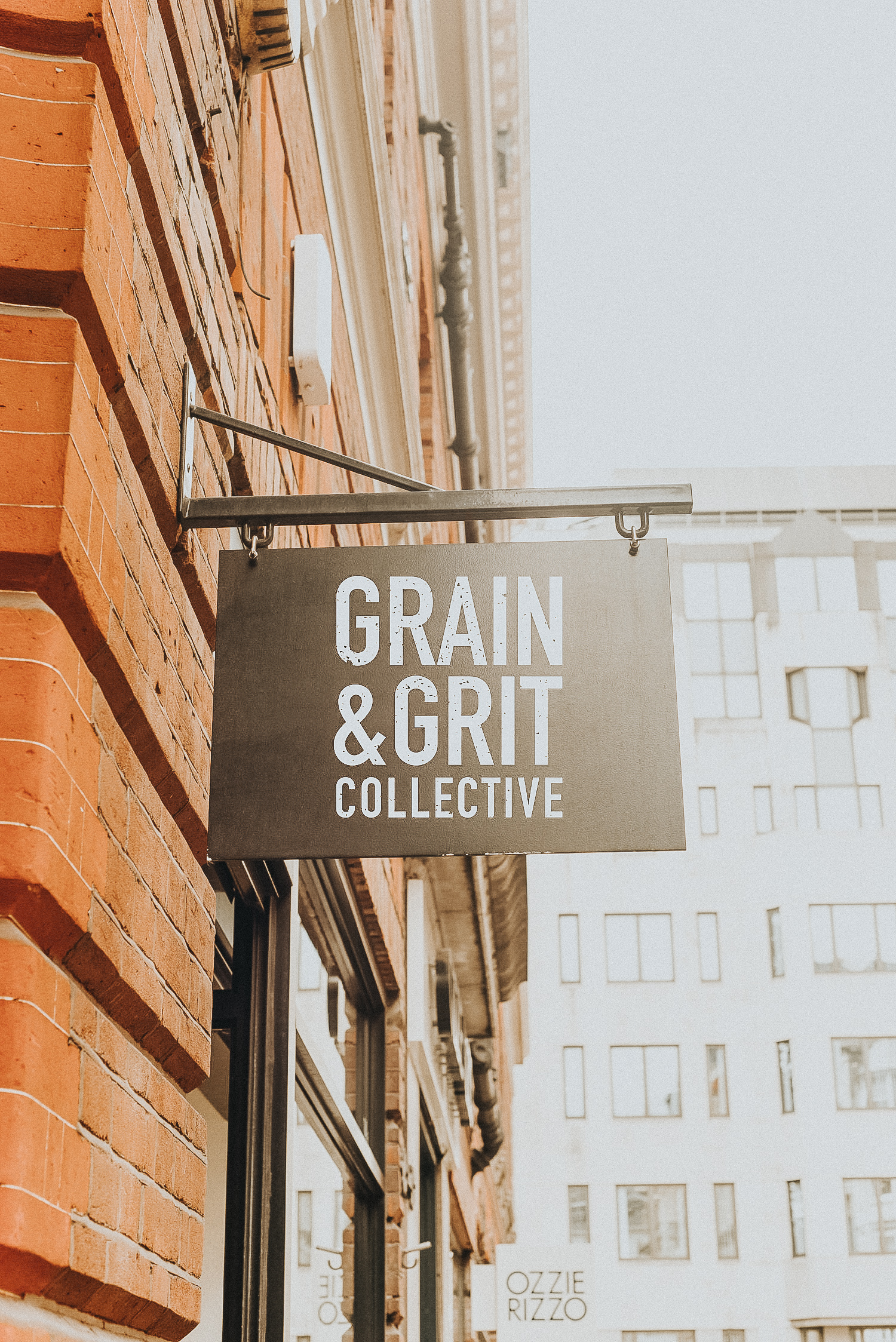 Bold masculine stamp clean modern simple typographic black and white logo for Grain & Grit Collective Restaurant Group in San Diego designed by Gretchen Kamp. Displayed on signage on a brick building. To view the full branding project, click here: http://www.gretchenkamp.com/grain-grit