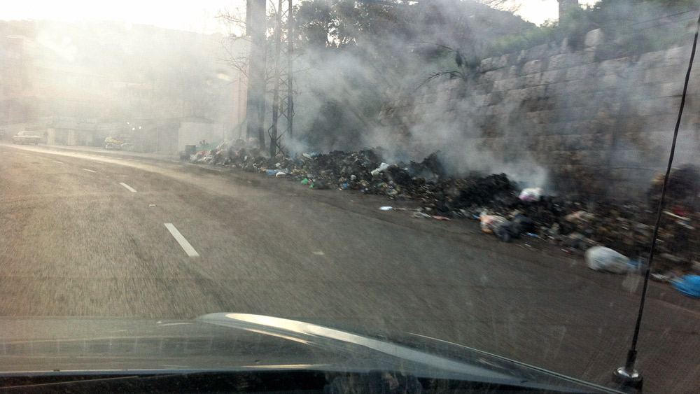 Piles of burning garbage along the road in Lebanon.