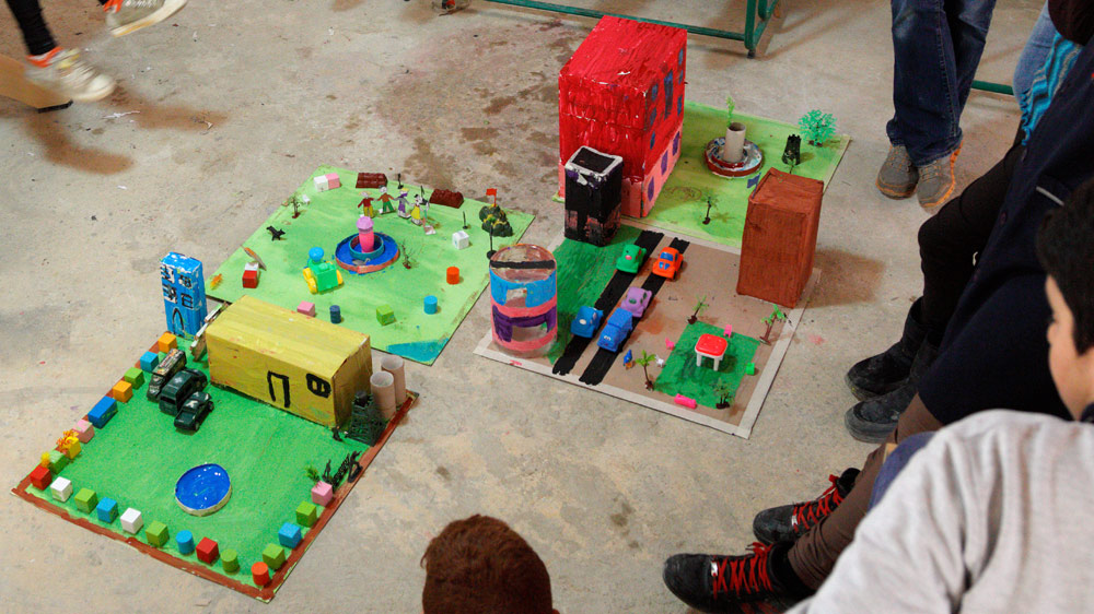 """The completed """"good"""" city with a school (guarded by soldiers), a park with children playing, homes with cars driving by, and a hospital tower with fountain in front."""