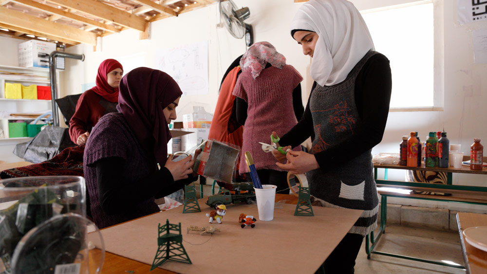 """Girls working on a """"bad"""" city diorama using recycled materials and leftover, unused toy props. Often to get one specific toy, an entire bag or set had to be purchased,making for a lot of leftover pieces. Anything not used in War-Toys photos or these sessions were donated to Kayany Foundation schools."""