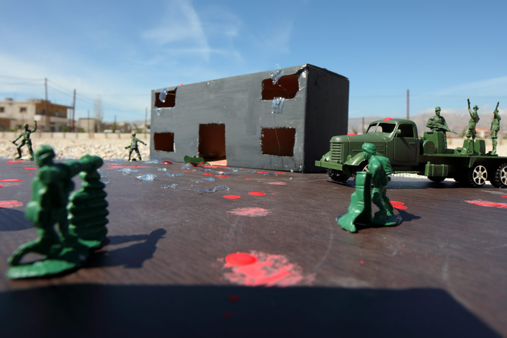 The blown up shell of a school, now at the center of a fight between soldiers. Blood spatters the ground in-between.