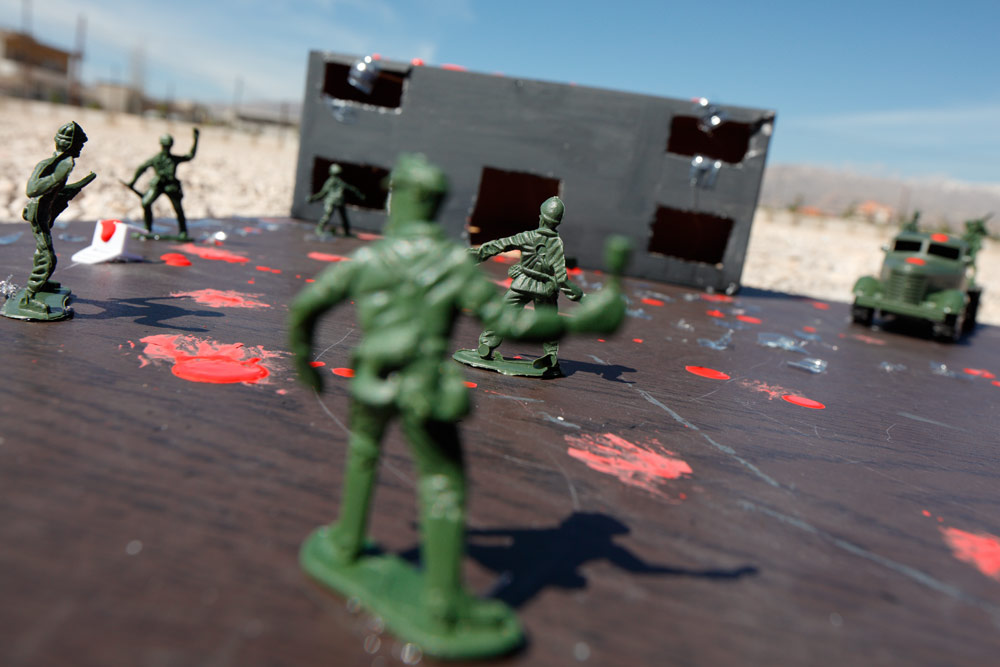Soldiers fighting over the remains of a school. Pieces of plastic bottles were used for the shattered windows.