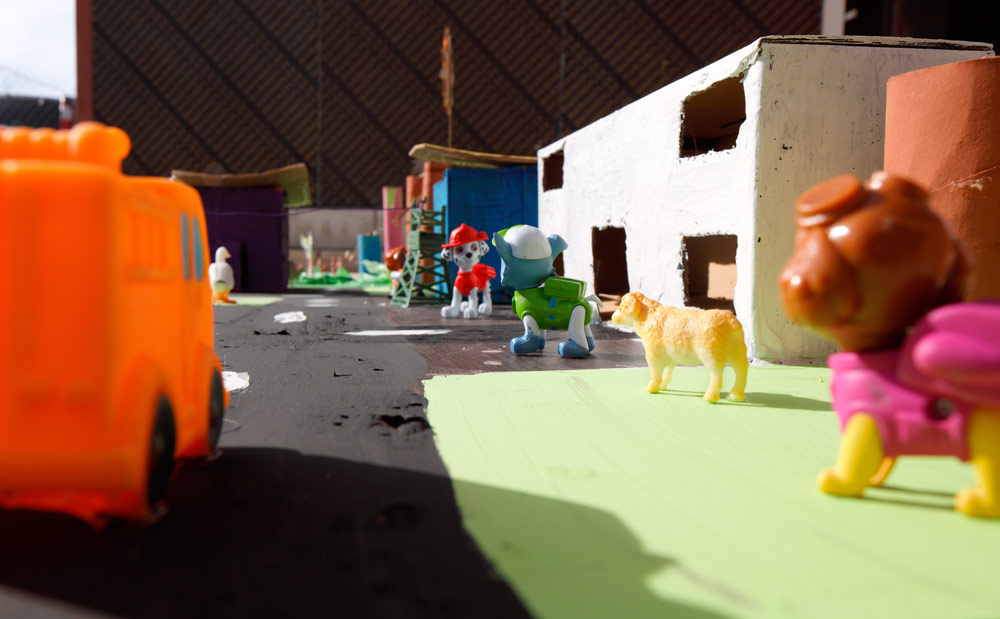 """Closeup of the school and surrounding area filled with happy people...portrayed by bootleg """"Paw Patrol"""" toys."""