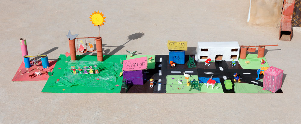 """The girls designed their final, idealized city dioramas to fit together, forming one collaborative piece. The little extra playground on the end was made by a small, welcomed addition to our group. The girl's mother worked at the school, and the 6-year-old refugee quietly yet confidently staked out a spot to work on her own diorama of a """"happy place"""" guarded by soldiers."""