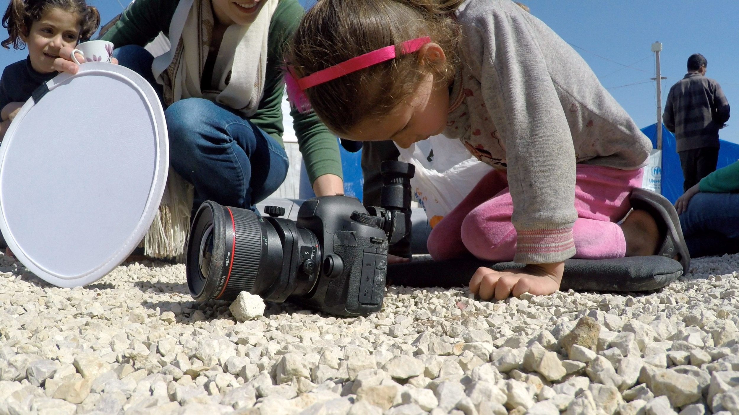 Refugee children take turns looking through the viewfinder at the toy-filled world created in front of the lens.