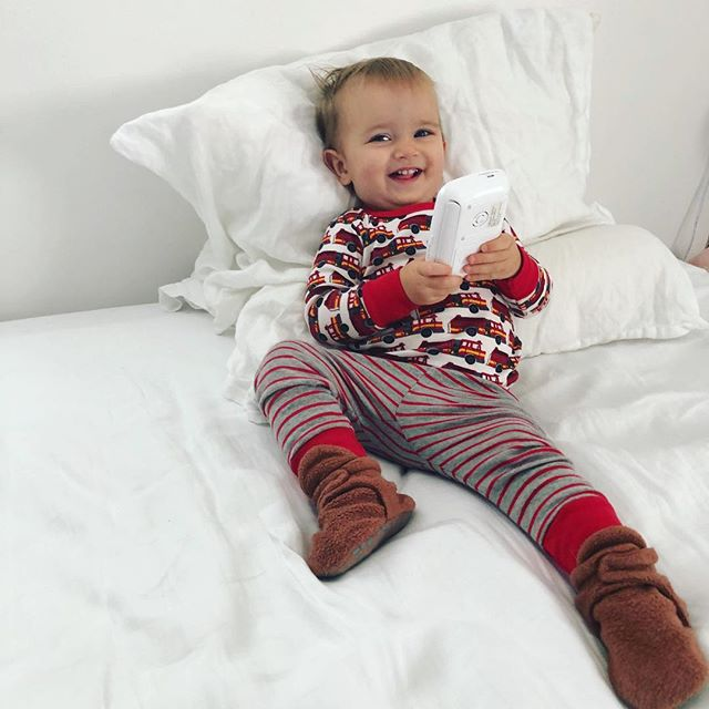 A portrait of my child in his favorite fire truck pajamas he asks for every night by making a siren sound and pointing at his chest, pushing buttons on something, lounging and playing on mama's bed. Oh and smiling! My love ❤️