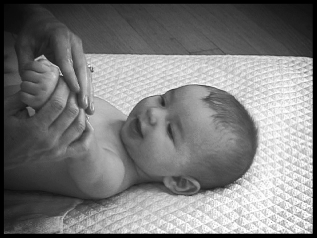 massaging baby's arms and hands