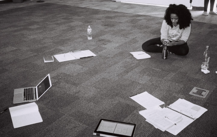 Maribel and papers and devices during a rehearsal break
