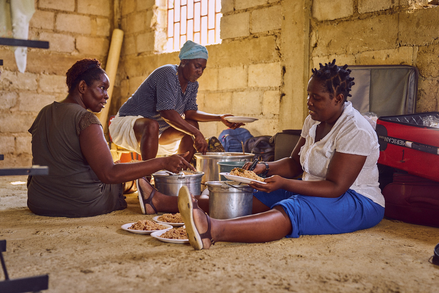 School Administrator Chantal Dumera (right) preparing lunch with women from the community.