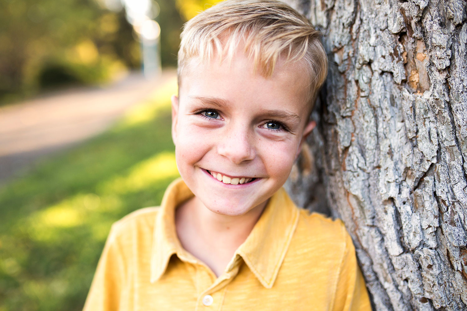 Boy leans on tree while smiling for photo during family photo session in Sacramento, California