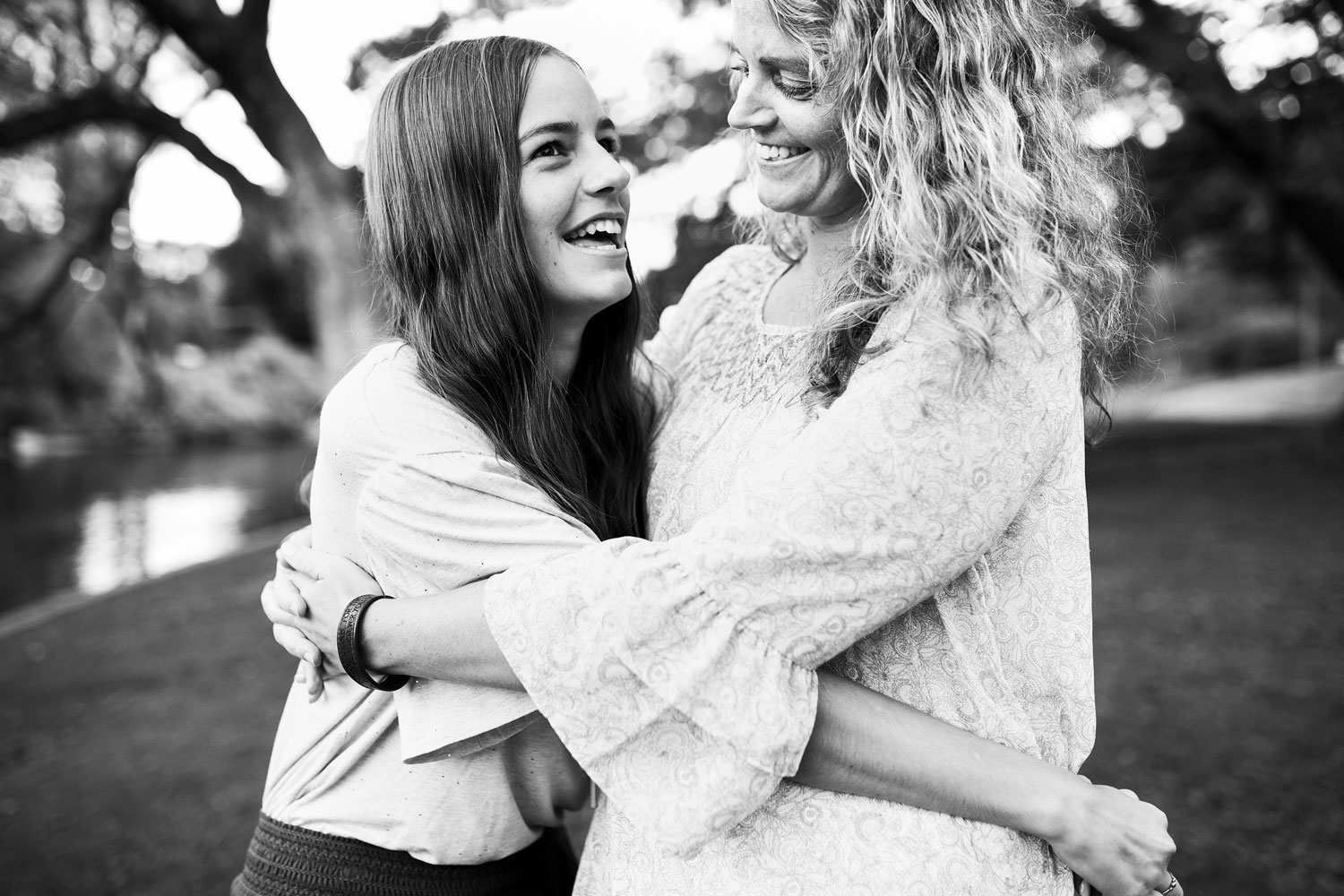 A mother and daughter hug and smile during a photo session at the UC Davis Arboretum