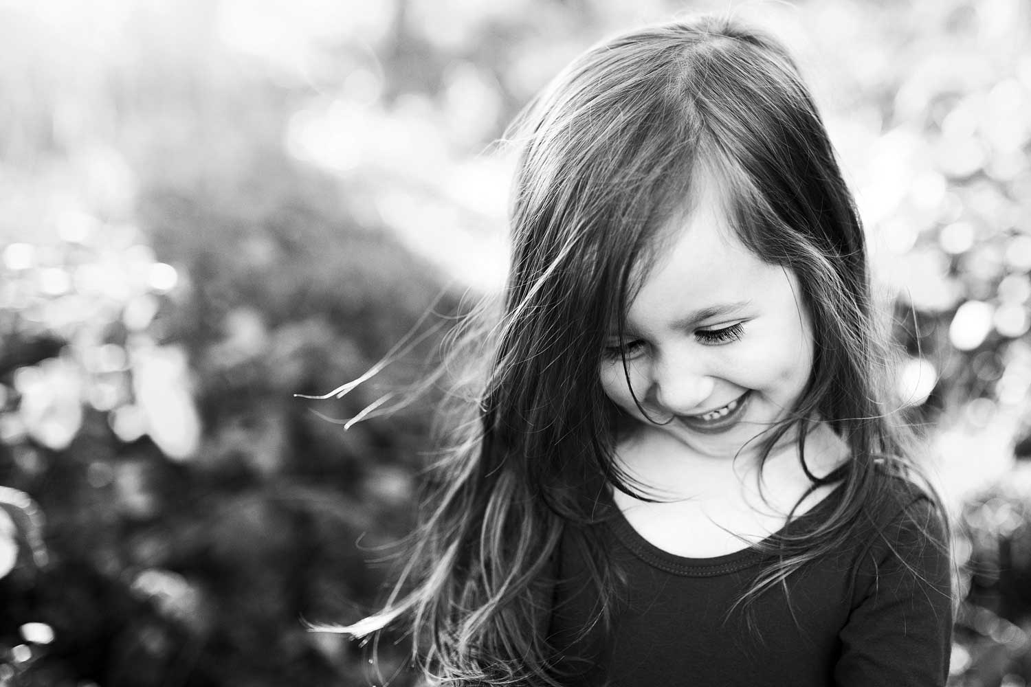 A young girl smiles as the wind blows in her hair during a photo session with Amy Wright Photography in Roseville, California.
