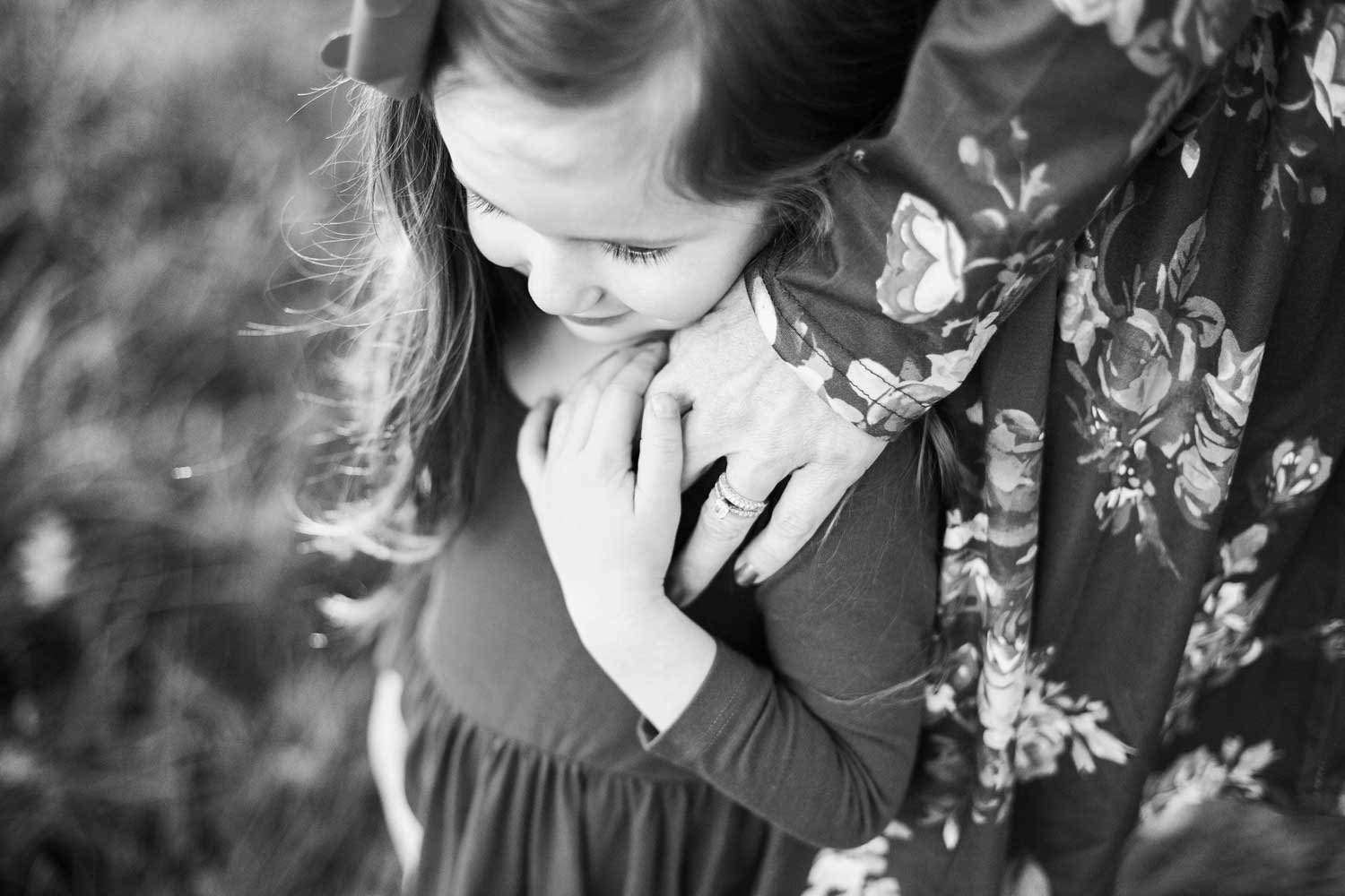Daughter holds Mother's hand as they embrace during a photo session with Amy Wright Photography.